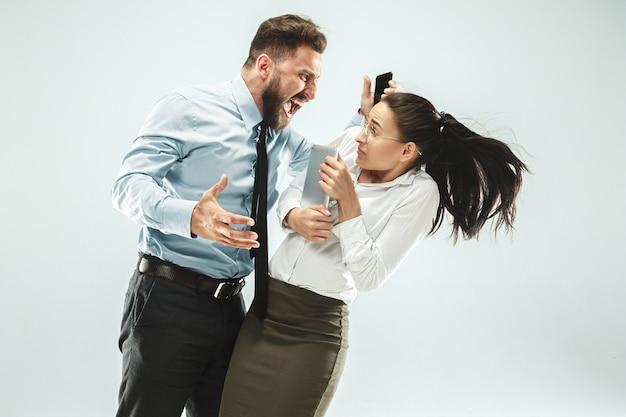 怒っているビジネスマンおよび彼の同僚のオフィス。