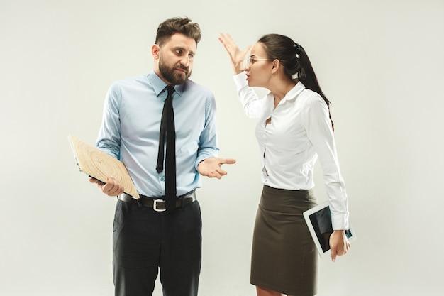 怒ったボス。事務所に立っている女性と秘書