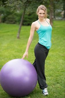 Молодая счастливая женщина с шариком фитнеса, напольным
