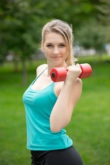 Спортивная девушка с гантелями в парке