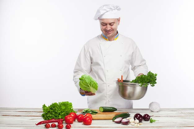 彼のキッチンで新鮮な野菜サラダを調理するシェフ