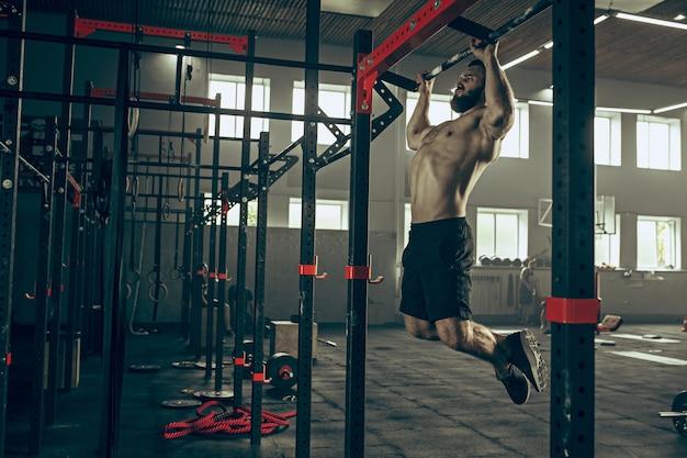 コンセプト:力、強さ、健康的なライフスタイル、スポーツ。ジムで強力な魅力的な筋肉男