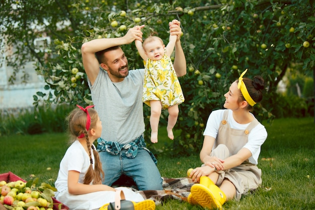 Счастливая молодая семья во время сбора яблок в саду на открытом воздухе