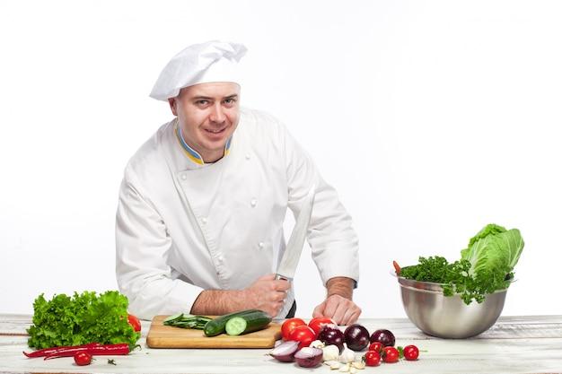 彼のキッチンでナイフでポーズのシェフ