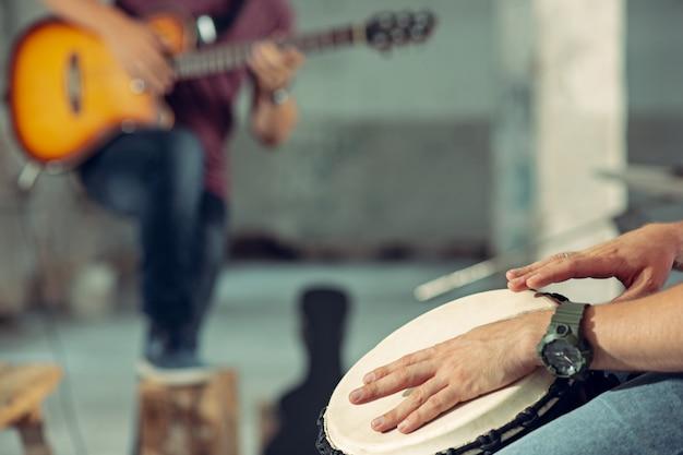 Повтор группы рок-музыки. электрогитарист и барабанщик за ударной установкой.