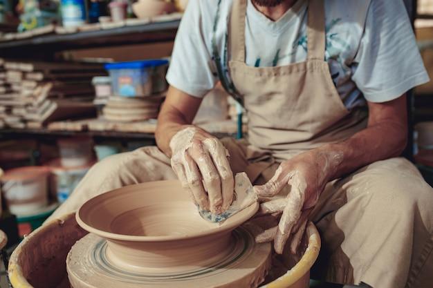 白い粘土のクローズアップの瓶または花瓶を作成します。マスター廃人。粘土の水差しマクロを作る男の手。