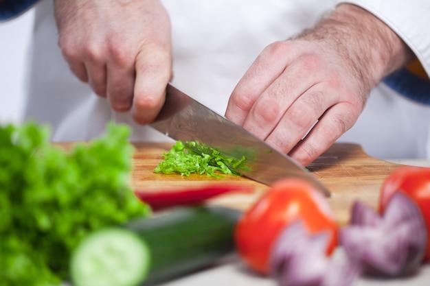 緑のレタスを彼の台所で切るシェフ
