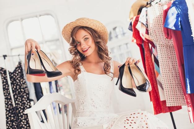 Молодая милая девушка выбирая и пробуя модельные ботинки на магазине