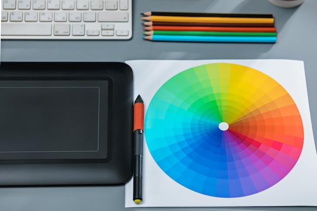 ラップトップ、空白のシート、メモ帳、花のポット、スタイラス、レタッチ用タブレット付きの灰色の机
