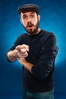 キャップ、カメラに向かって指している指の若い男
