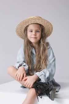 Стильная молодая девушка над серым