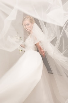 家のような白いスタジオインテリアで室内で立っている美しいドレスの花嫁。トレンディな結婚式スタイルのショット。探している入札入札のような若い魅力的な白人モデル。