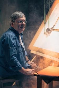 Зрелый креативный инженер, работающий над проектом на чертежной доске