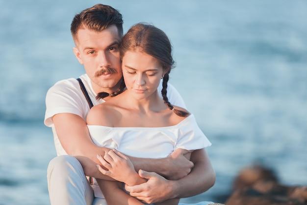 ビーチでリラックスして夕日を見て幸せな若いロマンチックなカップル
