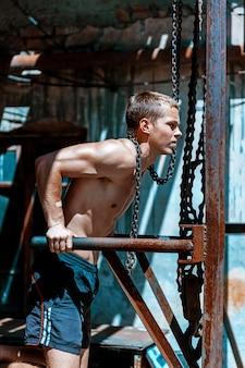 鉄の鎖に対していくつかの腕立て伏せをしている筋肉男