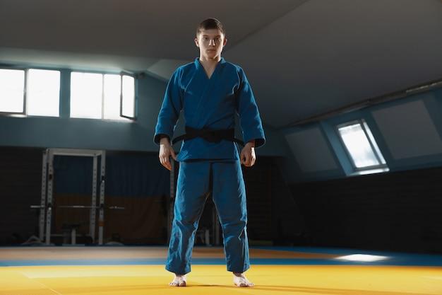 着物を着た若いファイターがジムで武道を訓練する