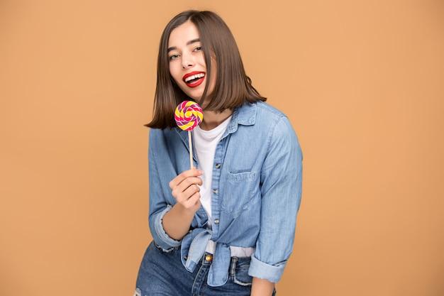 カラフルなロリポップを持つ若い女性