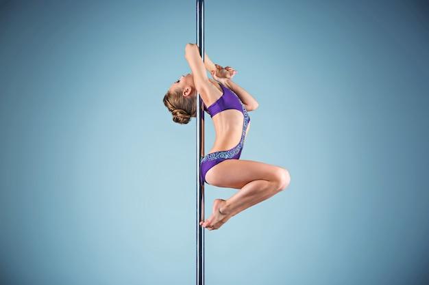 Сильная и грациозная молодая девушка, выполняющая акробатические упражнения на пилоне