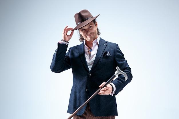 杖を保持しているスーツと帽子の成熟した男。