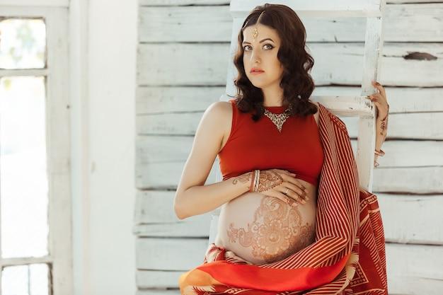 Живот беременной женщины с тату хной