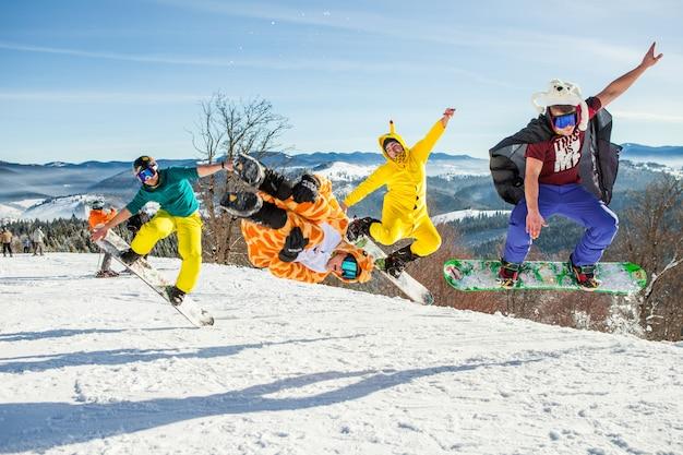 山を背景に彼のスノーボードでジャンプする男性ボーダー