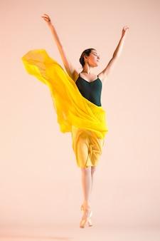 若くて信じられないほど美しいバレリーナがスタジオで踊っています