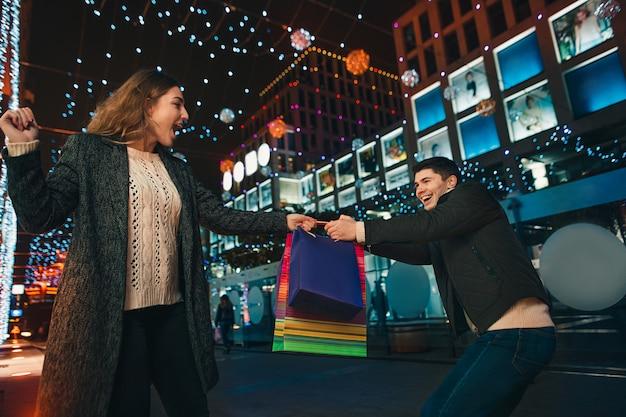 街で夜を楽しんでいる買い物袋と幸せなカップル