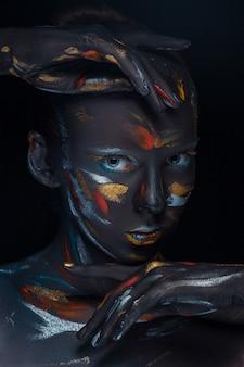 Молодая женщина, которая позирует покрыта черной краской