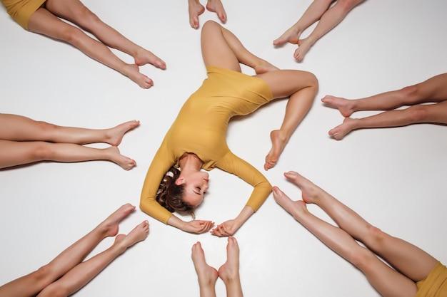 Группа современных артистов балета, лежащих на полу