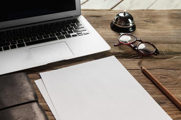 ノートパソコン、白紙、グラス、木製のテーブルに小さなベル