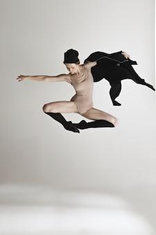 グレーの上で踊ってベージュの水着で若い美しいダンサー