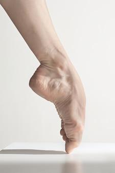 白い床にバレリーナの足をクローズアップ