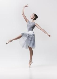 白で隔離される若いクラシックダンサー。