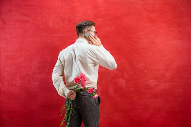 背中の後ろにカーネーションの花束を持って男