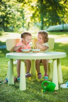 Две маленькие девочки сидят за столом и едят вместе на зеленой лужайке