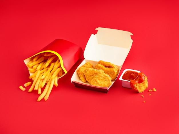 Куриные наггетсы и картофель фри на красном
