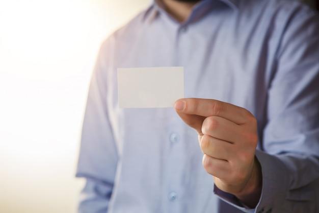 Мужчина держит белую визитку