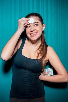 Молодая девушка держит фишки для покера на синем