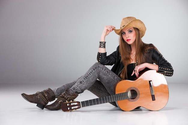 Красивая девушка в ковбойской шляпе и акустической гитаре.