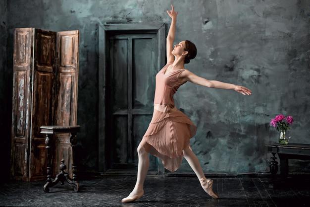 若くて信じられないほど美しいバレリーナがポーズとダンスをしている