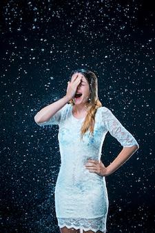 Молодая девушка стоит под струей воды