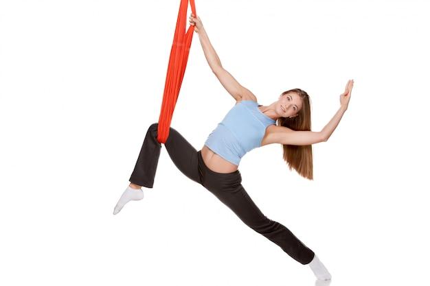 反重力空中ヨガを行う若い女性