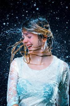 流水の下で立っている若い女の子