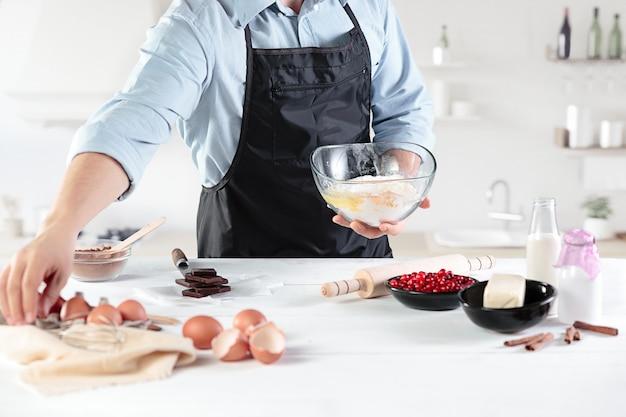 男性の手を背景に素朴なキッチンで卵を調理する