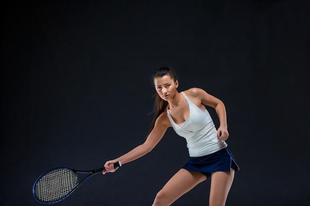 Красивая девушка теннисистка с ракеткой на темном фоне