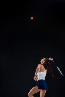 暗い背景にラケットで美しい少女テニスプレーヤー