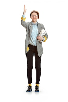 ホワイトスペースで分離された本を持って幸せな笑顔の女子学生の完全な長さの肖像画