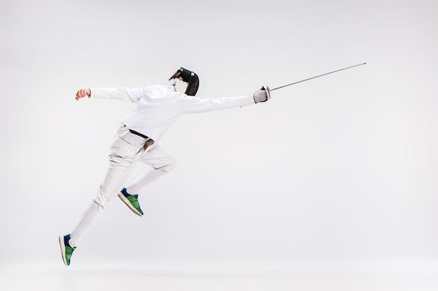Мужчина в фехтовальном костюме тренируется с мечом