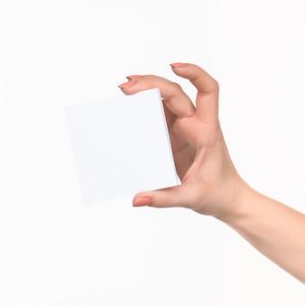 白のレコードの空白の紙を持っている女性の手。