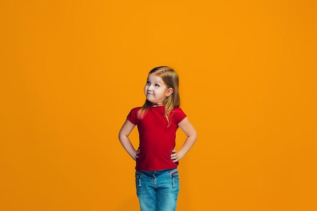 Счастливая предназначенная для подростков девушка стоя и усмехаясь против оранжевого космоса.
